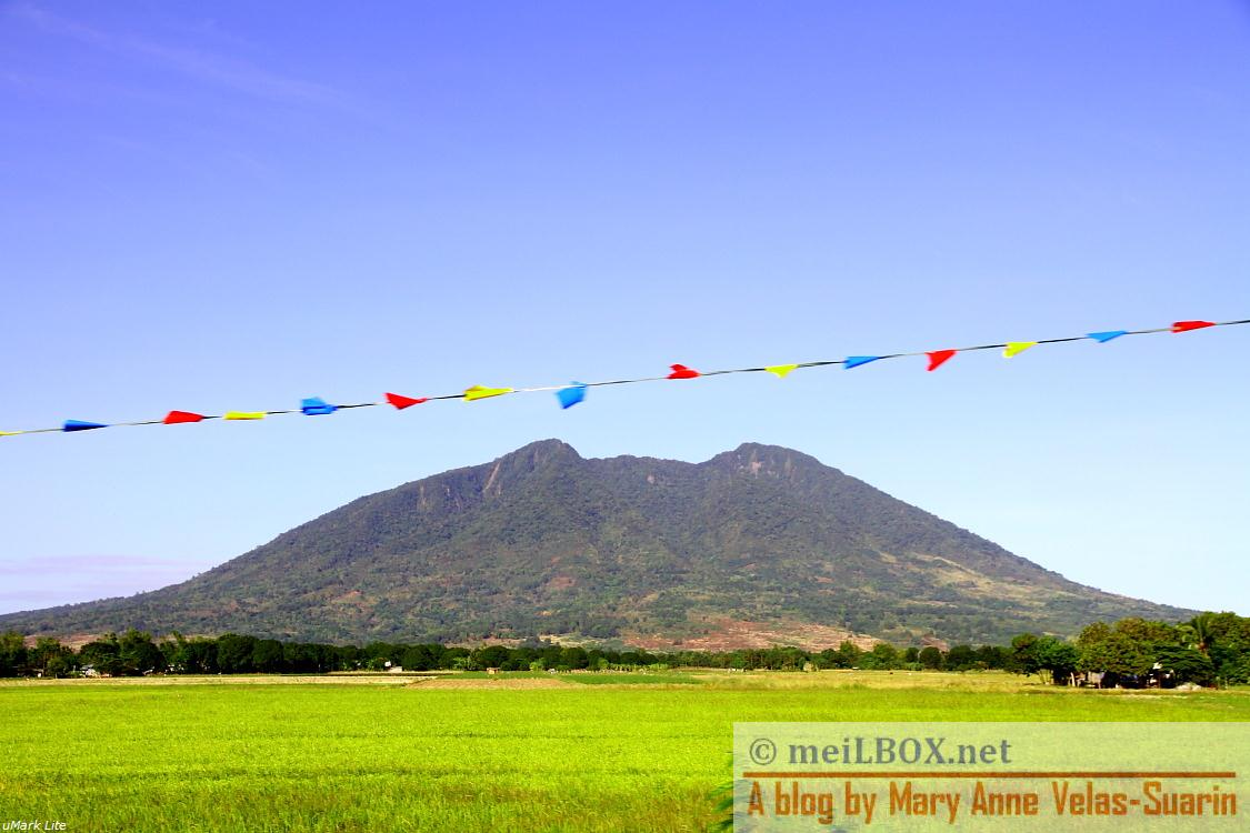 "Enroute to Nueva Vizcaya, I was able to capture this picture of Mt. Arayat (Pampanga) from the vehicle's window. The ""banderitas"" added more charms to the beauty of the mountain. :) [Photo taken by Mary Anne Velas-Suarin)"