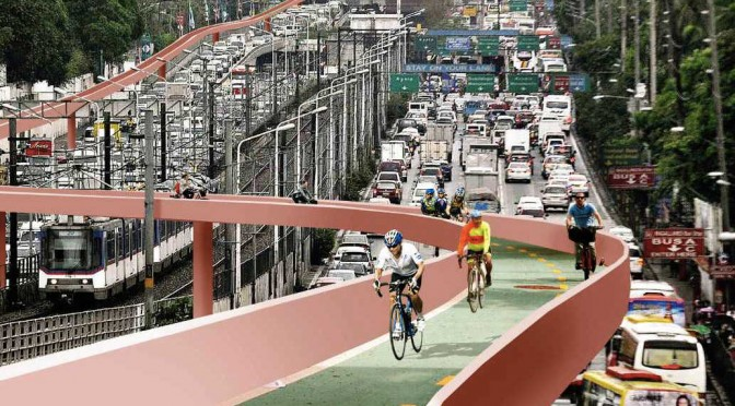 "The image of EDSA, used as ""backdrop,"" is courtesy of Richard Reyes/Philippine Daily Inquirer. The modified version of the same image—where an image of a prospective elevated bike lane is super-imposed—is courtesy of Anders Berensson Architects of Sweden. The bike lanes envisioned by this author will have protective roofs and railings for added security. A future work will calculate if putting solar panels on the roofs will be viable."